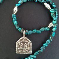 Ein indisches Silberamulett ist umgeben von kleinen Türkisen und 4 versilberten Zwischenteilen