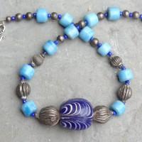 Große gefederte Jatimperle aus Java, hellblaue Glasperlen aus Westafrika und traditionelle Silberelemente aus Indien