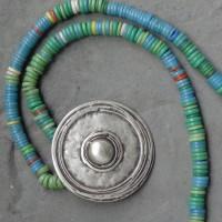 Glasscheiben in Grün, Gelb, Blau, sogenannte Cancaba Handelsperlen, frühes 20. Jh, Europa, und ein großer versilberter Anhänger aus Anatolien