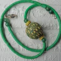Sehr kleine , grüne Bakelit Scheiben, ursprünglich aus Europa, jetzt aus Ghana , umspielen eine Glasperle aus Timor, Sie ist nach alten Vorlagen gefertigt.