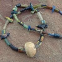 Versteinerter Sanddollar, Elfenbeinküste, an einer Kette aus Glaselementen, die aus einer römischen Glasmanufaktur des 5.-6. Jhs. im heutigen Afghanistan stammen sollen.