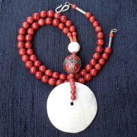 """Eine große """"Sacred Chunkshell"""" – Scheibe aus dem Himalaya und ein traditionelles afghanisches Element mit Korallen (?) Einlagen hängen an einer Kette aus polierten Schaumkorallen"""